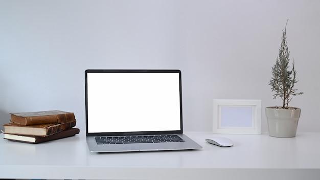 Laptop do computador, planta da casa, moldura e livros na mesa branca.