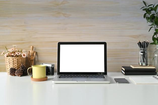 Laptop do modelo do espaço de trabalho, caneca de café, livros e materiais de escritório no trabalho de mesa.