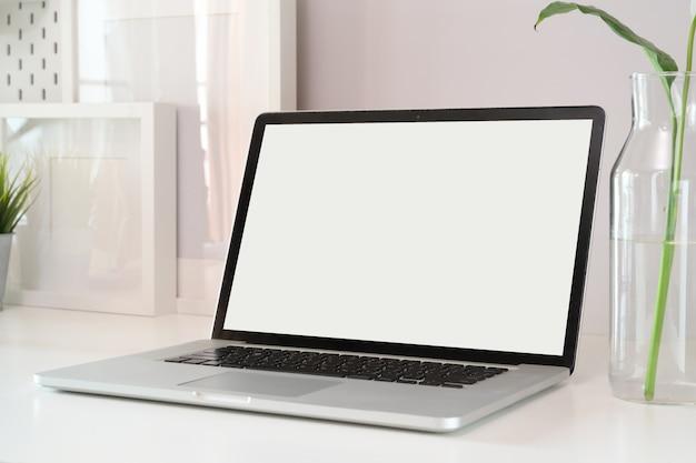 Laptop do modelo no espaço de trabalho de madeira branco.