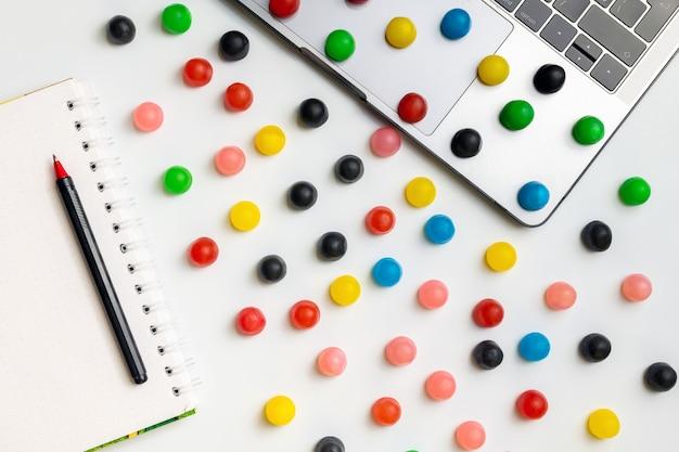 Laptop, doces coloridos e pasta de trabalho com chocolate e café no local de trabalho.