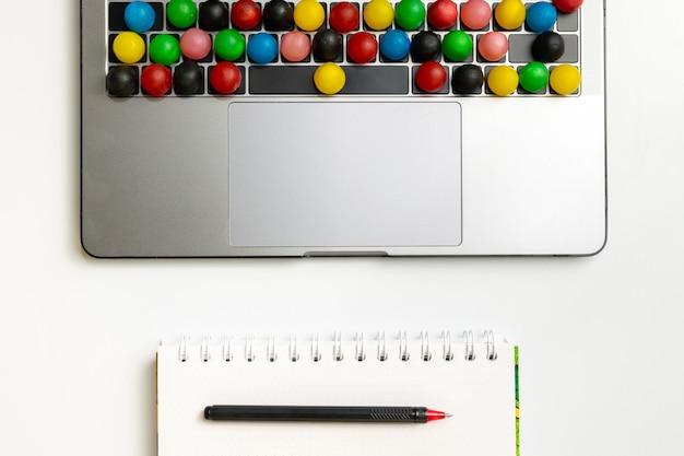 Laptop, doces coloridos no teclado e pasta de trabalho com chocolate e café no local de trabalho.
