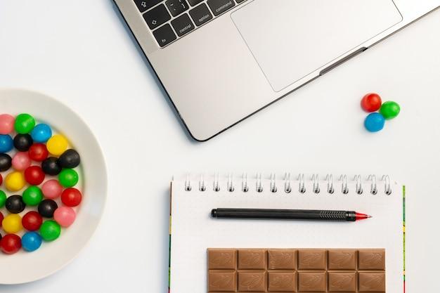 Laptop, doces e pasta de trabalho com barra de chocolate e café no local de trabalho.