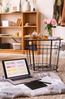 Laptop e bloco com caneta na manta perto da pequena mesa com chá de ervas e rosas cor de rosa no chão com estante