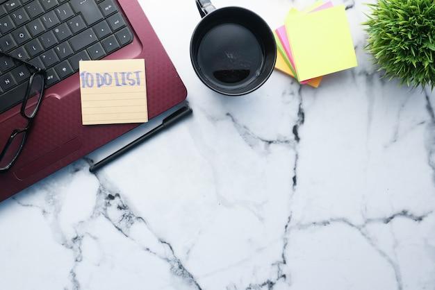 Laptop e bloco de notas com a lista na mesa de escritório.
