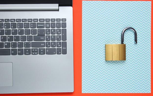 Laptop e cadeado em papel laranja e azul