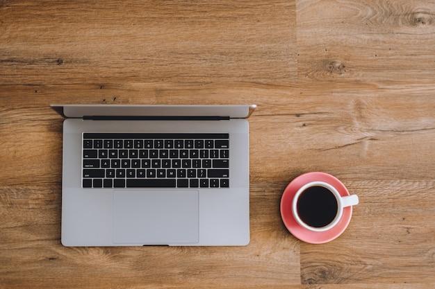 Laptop e café isolados em um fundo de madeira com espaço de cópia
