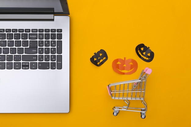 Laptop e carrinho de compras com abóboras de halloween de corte de papel em um fundo amarelo. tema de halloween. vista do topo