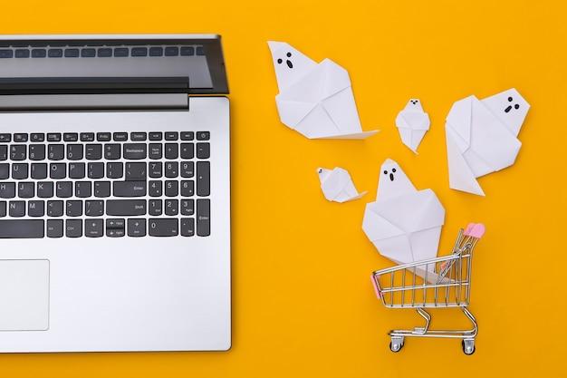 Laptop e carrinho de compras com fantasmas de origami em fundo amarelo. tema de halloween. vista do topo