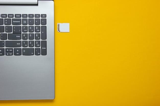 Laptop e cartão de memória sd em papel amarelo com formas geométricas