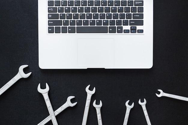 Laptop e chave inglesa em fundo preto, vista superior, configuração plana