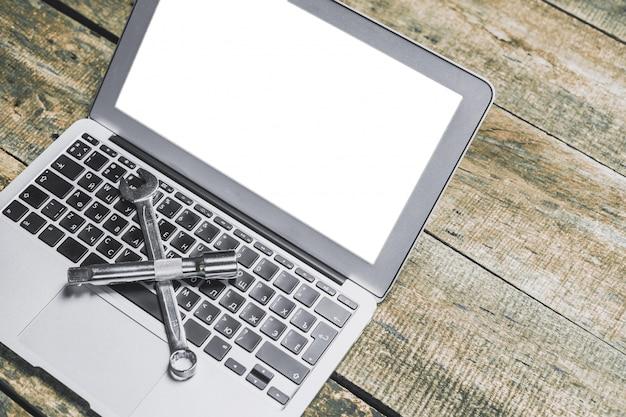 Laptop e chave inglesa no velho rústico