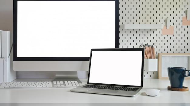 Laptop e computador isolaram a tela branca na tabela do espaço de trabalho.
