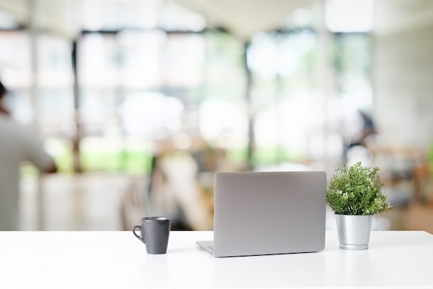 Laptop e copo de café na tabela branca no escritório.