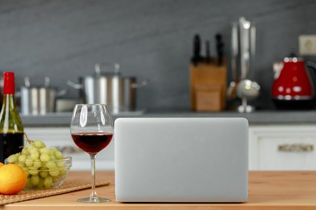 Laptop e copo de vinho tinto na mesa da cozinha de madeira