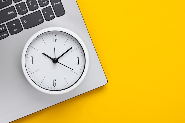 Laptop e despertador em fundo amarelo. o tempo está fugindo. o conceito de prazos urgentes no trabalho e compromissos. vista do topo. postura plana