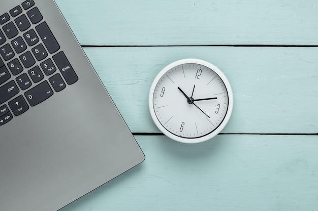 Laptop e despertador na superfície de madeira azul. o tempo está fugindo. o conceito de prazos urgentes no trabalho e compromissos. vista do topo