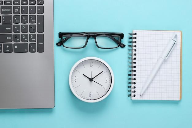 Laptop e despertador, óculos, caderno na superfície azul. o tempo está fugindo. o conceito de prazos urgentes no trabalho e compromissos. vista do topo