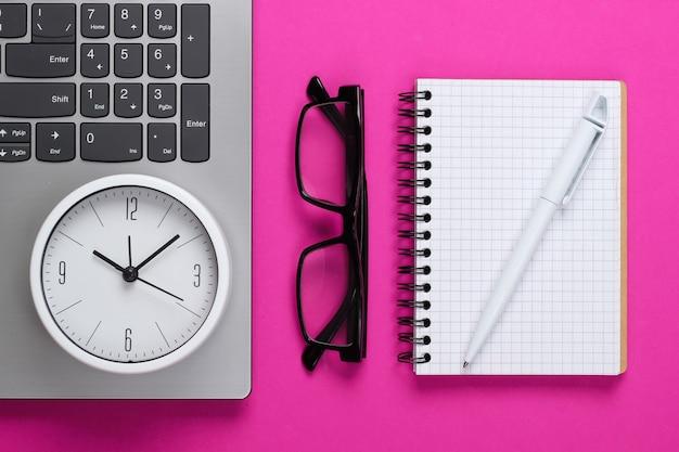 Laptop e despertador, óculos, caderno na superfície rosa. o tempo está fugindo. o conceito de prazos urgentes no trabalho e compromissos. vista do topo