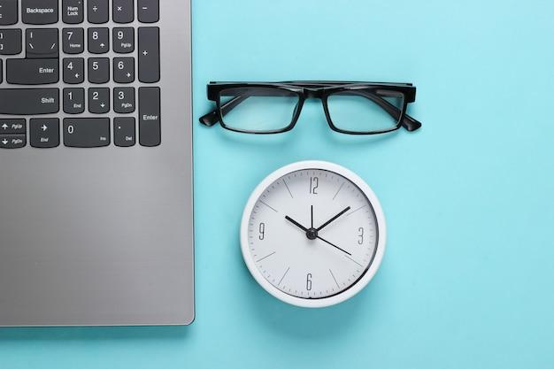 Laptop e despertador, óculos sobre fundo azul. o tempo está fugindo. o conceito de prazos urgentes no trabalho e compromissos. vista do topo