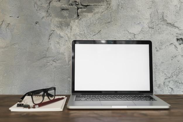 Laptop e espetáculo com papelaria de escritório na mesa de madeira com parede velha