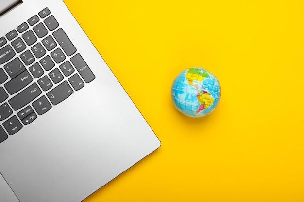Laptop e globo na superfície amarela
