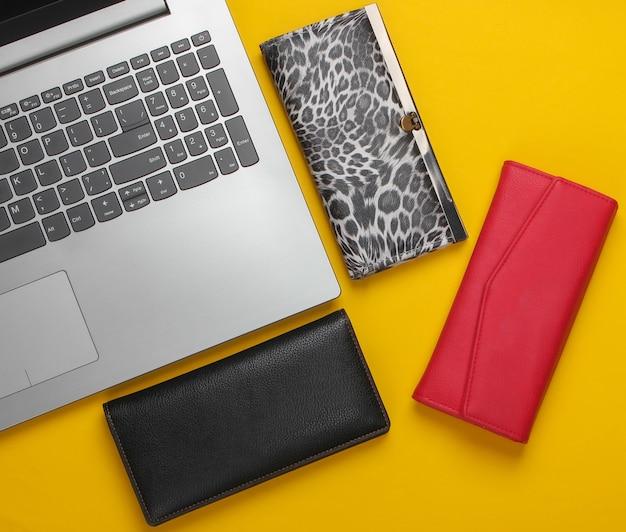 Laptop e muitas carteiras elegantes em um amarelo.