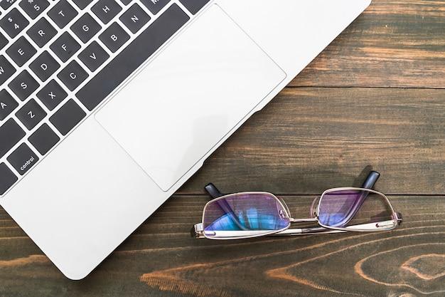 Laptop e óculos na mesa