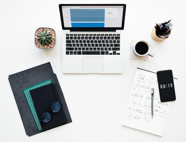 Laptop e papelaria na mesa de trabalho branco