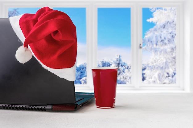 Laptop e presentes na mesa com chapéu de papai noel em casa com uma vista panorâmica