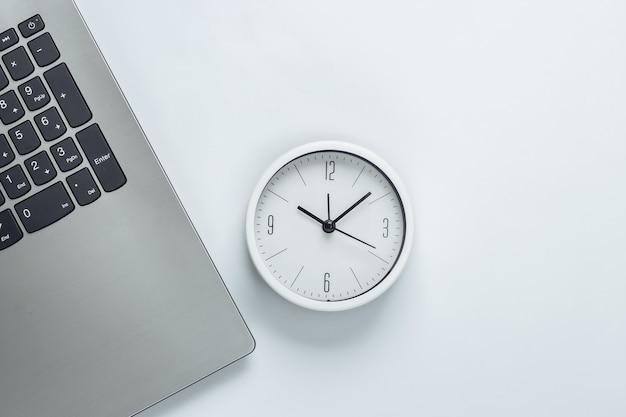 Laptop e relógio em fundo branco. o tempo está fugindo. o conceito de prazos urgentes no trabalho e compromissos. vista do topo