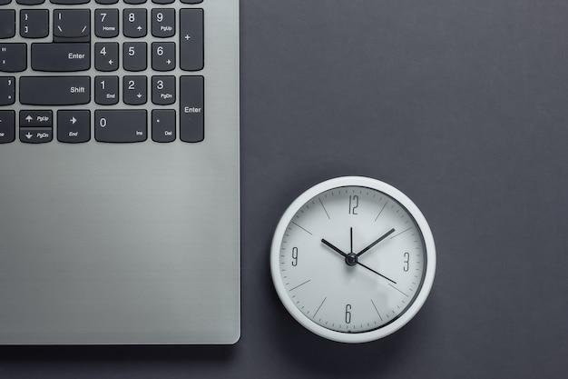 Laptop e relógio em fundo cinza. o tempo está fugindo. o conceito de prazos urgentes no trabalho e compromissos. vista do topo