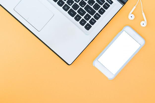 Laptop e smartphone com uma tela branca e fones de ouvido no fundo laranja