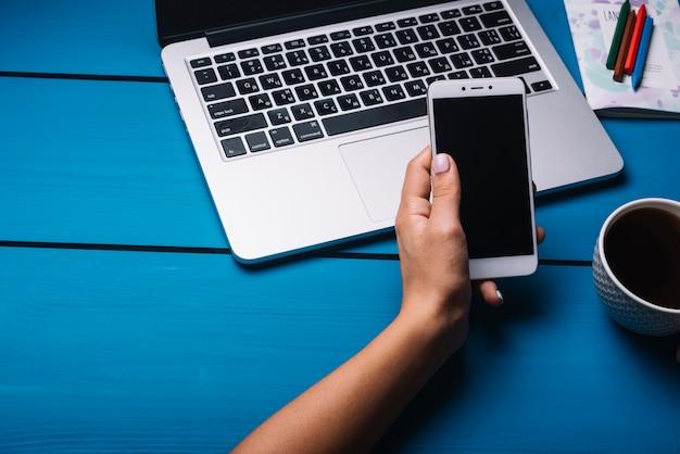 Laptop e smartphone na mesa azul com café