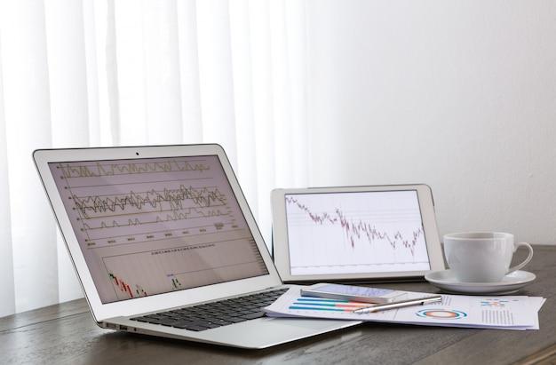 Laptop e tablet com relatórios de negócios