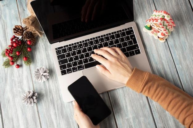Laptop e telefone com tela vazia para publicidade sazonal de natal