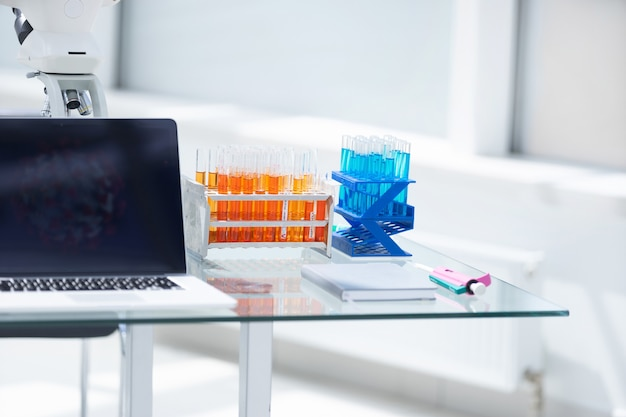 Laptop e tubos com testes na mesa do laboratório. ciência e saúde.