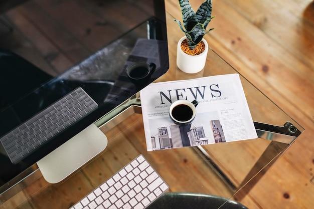 Laptop e um jornal sobre uma mesa