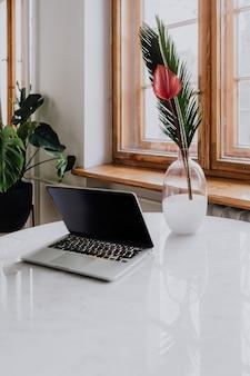 Laptop e um vaso em uma mesa de mármore