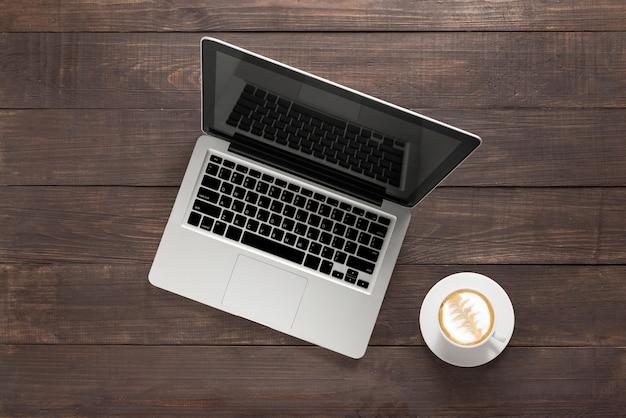 Laptop e uma xícara de café sobre fundo de madeira