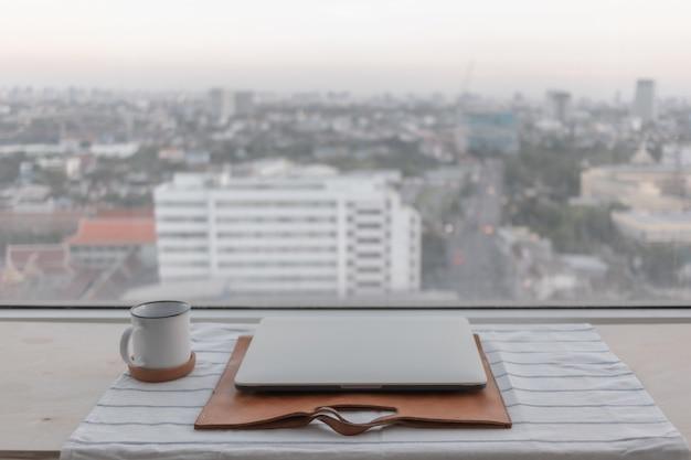 Laptop e xícara de café branco com vista da cidade conceito de trabalho em casa