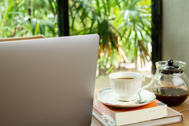 Laptop e xícara de café com o livro na tabela de madeira no café.