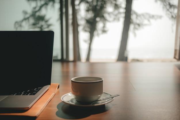 Laptop e xícara de café no chão de madeira