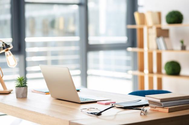 Laptop elegante em cima da mesa e sendo aberto para uso