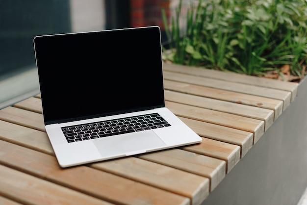 Laptop em um banco de madeira ao ar livre