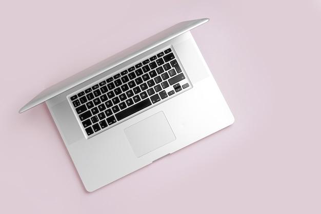 Laptop em um fundo rosa. trabalhe no conceito de casa. vista superior, configuração plana