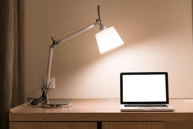Laptop em uma mesa com lâmpada