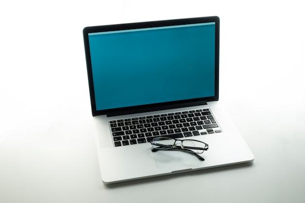 Laptop em uma mesa com óculos. pessoas que trabalham em casa