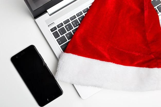 Laptop em uma parede branca e isolada. um chapéu de santaclaus encontra-se em um laptop. o fim do ano de trabalho. vendas de natal.