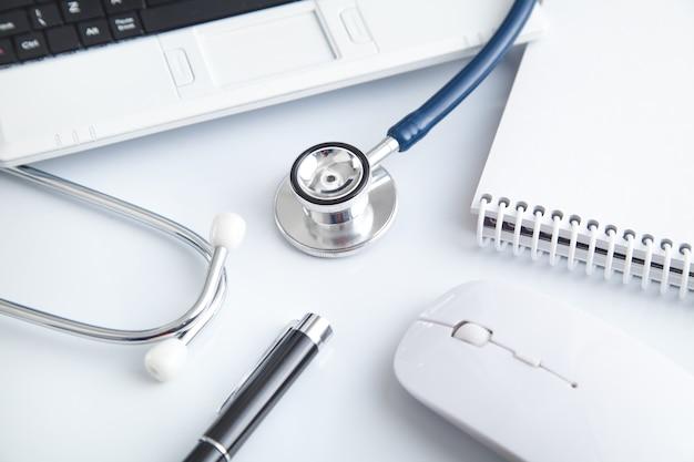 Laptop, estetoscópio, caneta, bloco de notas, mouse de computador. médico. o negócio