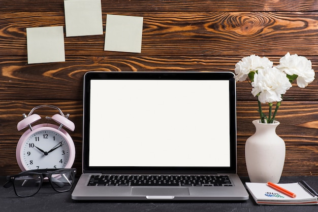 Laptop exibindo tela branca com vaso; lápis e bloco de notas na mesa